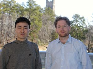 Two men pose in front of Duke Chapel